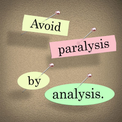 35288527 - avoid paralysis by analysis words in cut out papers pinned to a bulletin board as a saying or quote warning you not to overthink or be undecided by endless committee discussion
